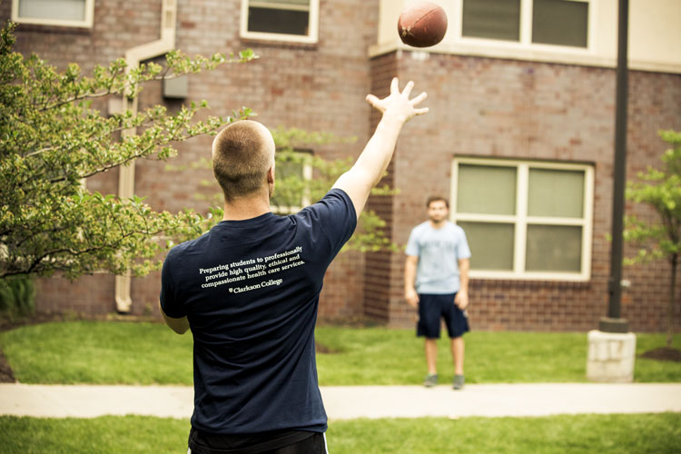 Students playing catch in the courtyard in front of the Residence Hall.